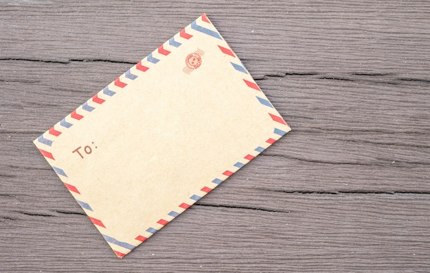 織り目加工の古い木製のテーブルの上の茶色のクローズアップ封筒