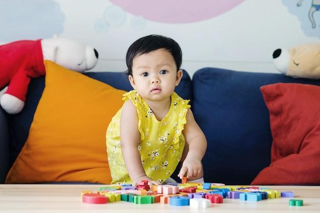 クローズアップ少女は、リビングルームのバックグラウンドでソファの上の木製のジグソーパズルのおもちゃを遊ぶ