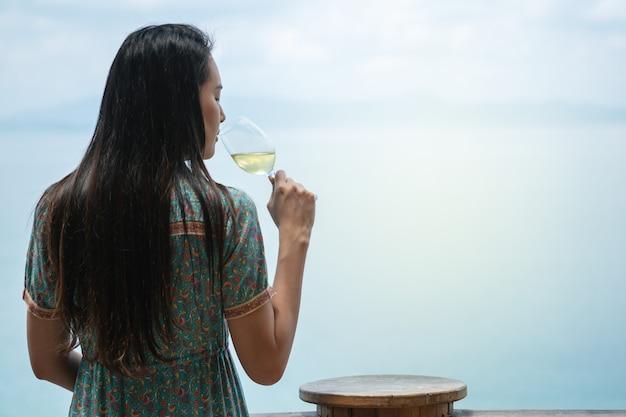 クローズアップ女性は海の景色を望むテラスでワインを飲みながら白ワインを飲む