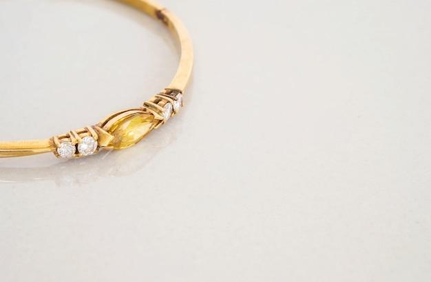Крупным планом золотой браслет с желтой галькой на сером мраморном камне