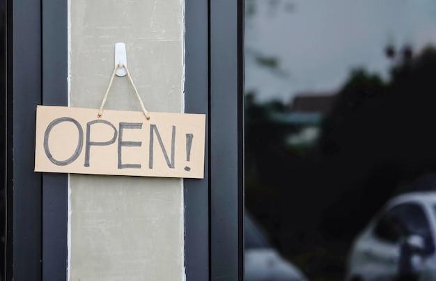 コーヒーショップの背景の前にオープンマッサージで茶色のハード紙看板をクローズアップ