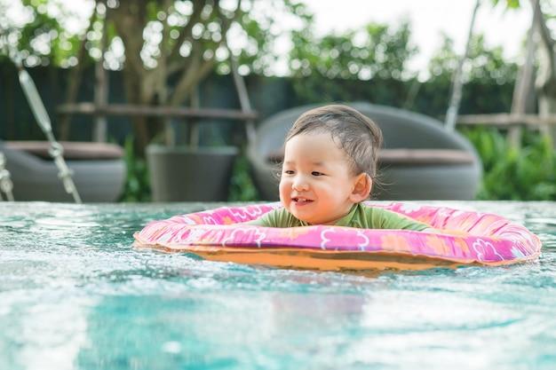 スイミングプールで子供のためのボートに座っている少年のクローズアップ