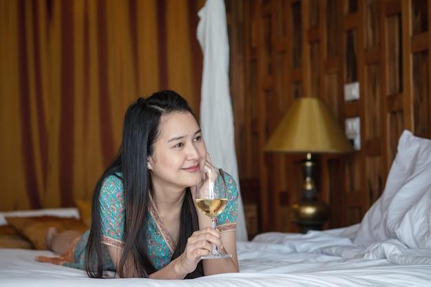 クローズアップ女性の寝室で白ワイングラスとベッドの上に横たわる