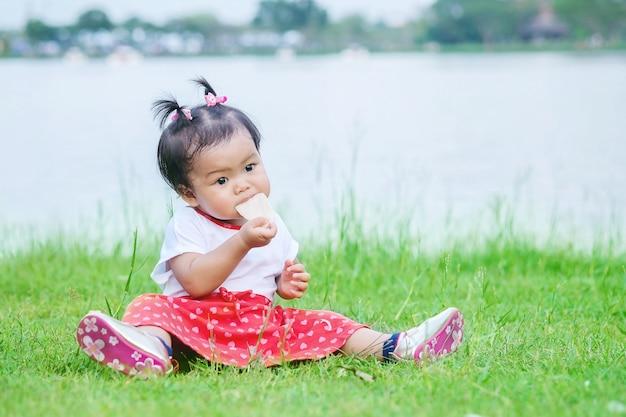 公園のバックグラウンドでクラッカーを食べる草の床の上に座っている少女のクローズアップ