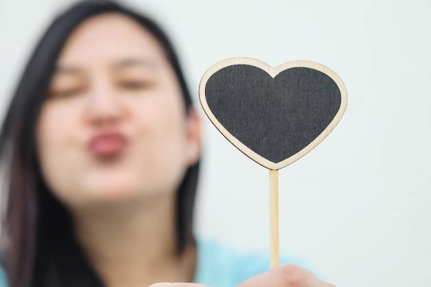 ぼやけたハート型のクローズアップの木製のブラックボードは、女性の背景のキス顔を送る