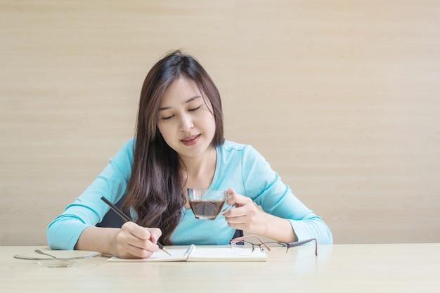 働く女性はカップでコーヒーを飲むために座る