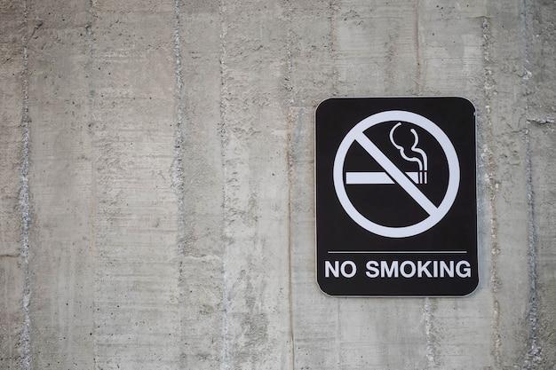 コピースペースを持つ古いセメント壁織り目加工の背景に禁煙の言葉でクローズアップ禁止標識
