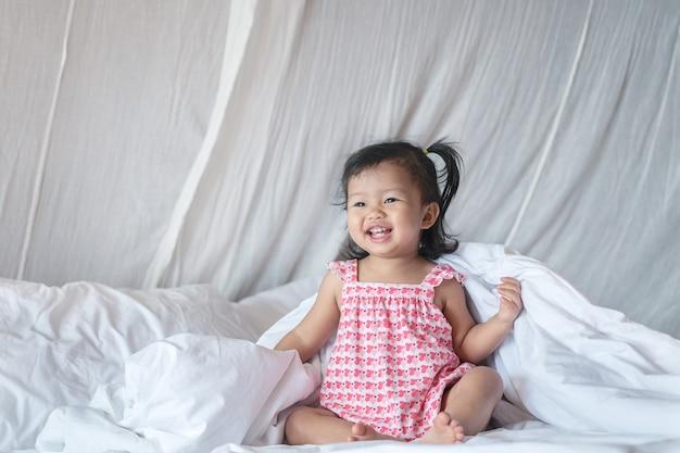 Крупным планом маленькая девочка сидит смеется на кровати в спальне