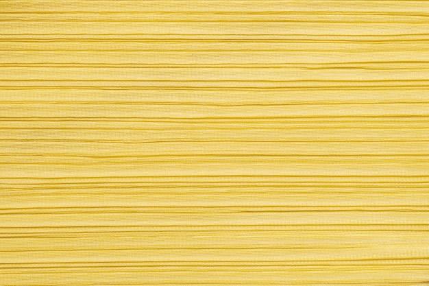質感の黄色の婦人服で抽象的なパターンをクローズアップ