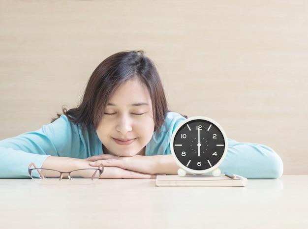 アジアの女性が休憩時間に幸せな顔を机の上に寝て時計で本を読んでから