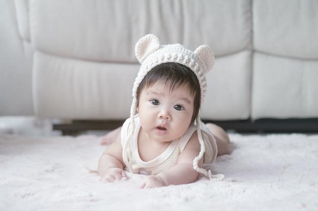 かわいいモーションでカーペットの上に横たわるアジアの女の赤ちゃんのクローズアップ