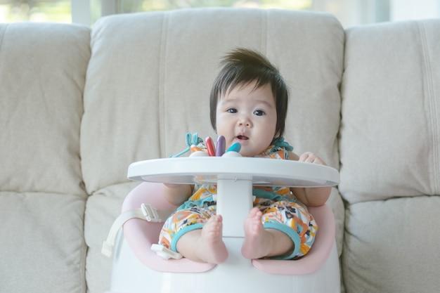 クローズアップ小さな女の子が子供のための椅子に座る