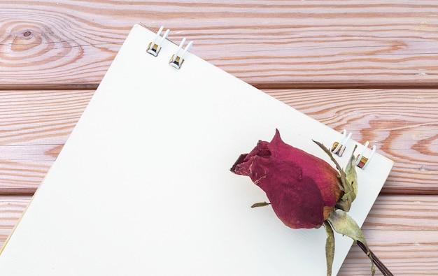 コピースペースを持つ木製デスクテクスチャ背景に白いメモ用紙とクローズアップ乾燥赤いバラ