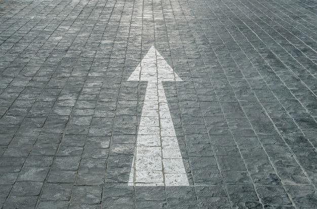 表面の古くて淡い白塗りの矢印が駐車場で黒いレンガ石造りの床にサインオンします。