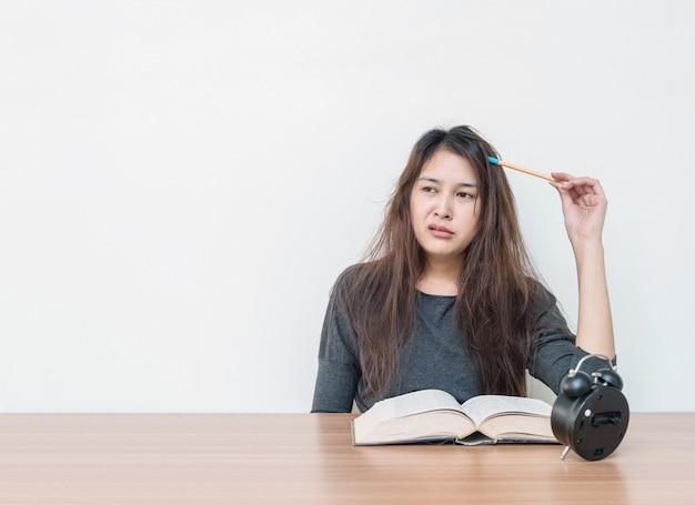 Женщина крупного плана азиатская утомленная от читать книгу с скучной эмоцией стороны в концепции работы