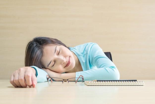 アジアの女性は、本を読んでから休憩時間に幸せそうな顔で机に横になって寝る