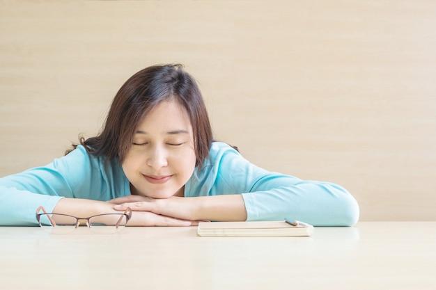 アジアの女性は、本を読んでから休憩時間に幸せそうな顔で机の上に寝て