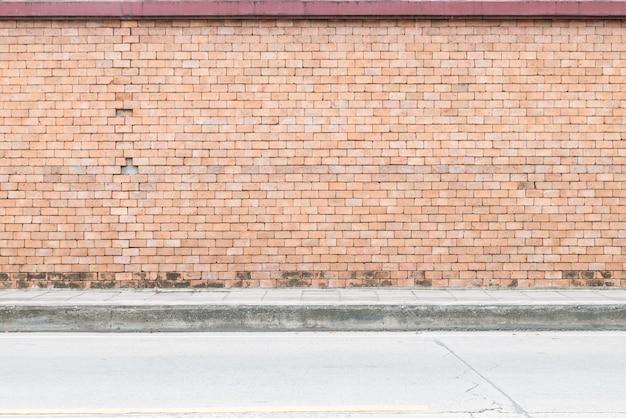 通りの床の織り目加工の背景を持つ古い茶色のレンガの壁でレンガパターンのクローズアップ表面