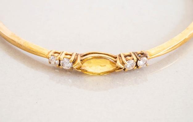 Крупным планом золотой браслет с желтой галькой на сером фоне мраморного камня