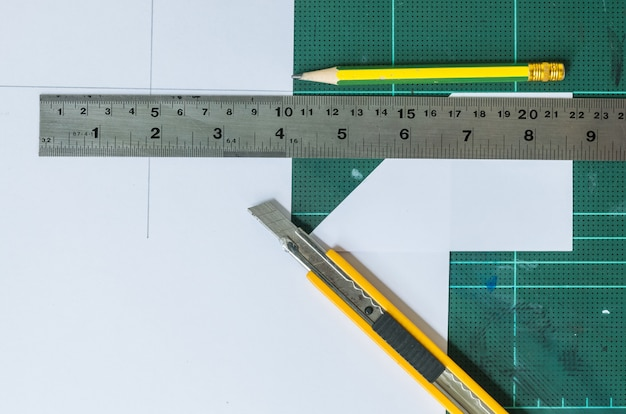 Резак, деревянный карандаш и линейка на фоне старых зеленых резиновых прокладок