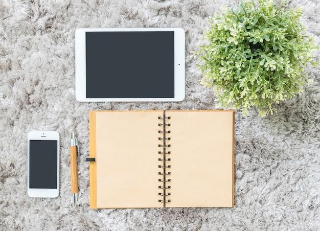 Крупным планом коричневый блокнот, коричневая ручка, компьютерная тетрадь, планшет, телефон и искусственное растение на серой ткани