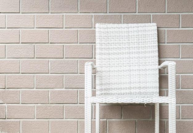 レンガの壁のテクスチャ背景にクローズアップの木製織り椅子