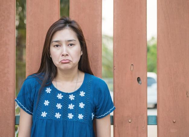 木製のフェンスの背景に悲しい顔を持つアジアの女性
