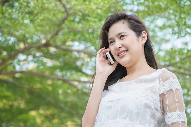 アジアの女性が公園で携帯電話で話しています。