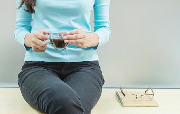 Азиатская женщина отдыхает пить кофе в свободное время на деревянный стол