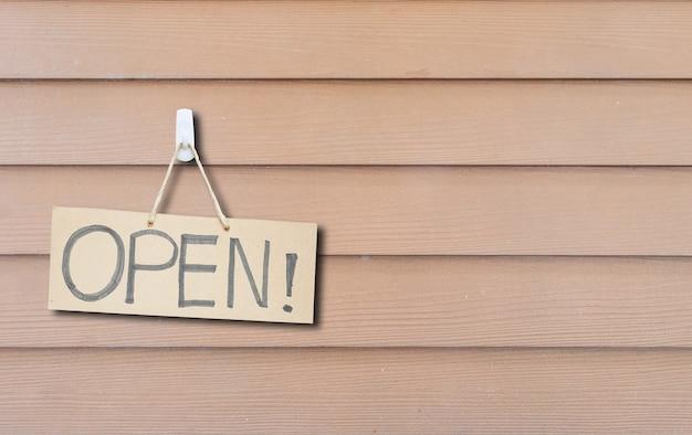 茶色の木製の壁のテクスチャのオープンメッセージと茶色のハード紙看板をクローズアップ