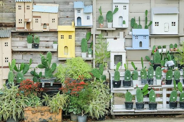 Украшение крупного плана на старой деревянной стене дома кактусом и коробкой в форме дома
