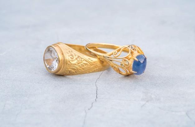 ぼやけているセメントの床の背景にクローズアップ古いダイヤモンドと青い小石リング
