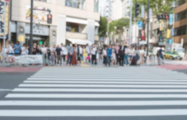 横断歩道で通りを渡って待っている群衆のモーションブラー