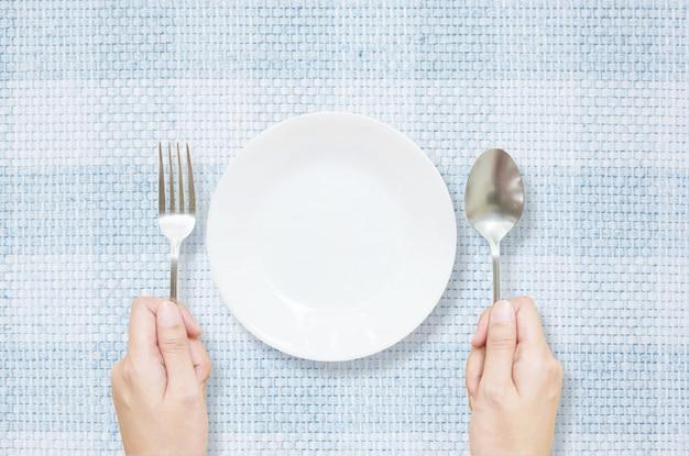 Крупным планом белое керамическое блюдо с нержавеющей вилкой и ложкой в руке женщины на синем фоне ткани текстурированный мат
