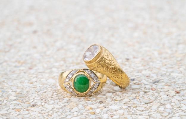 ぼやけた石造りの床の背景にクローズアップの古いダイヤモンドの指輪
