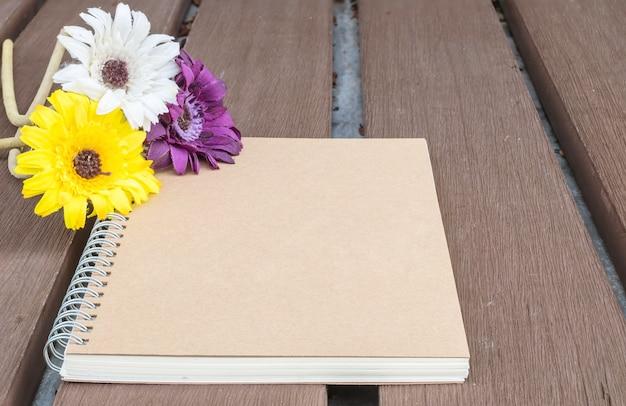 ぼやけた古い木製のテーブルテクスチャ背景にカラフルな偽花とクローズアップ茶色のメモ帳
