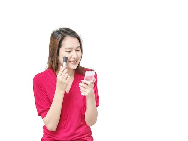 クローズアップアジアの女性は化粧品の概念で白い背景に分離されたプレス粉で補っています。