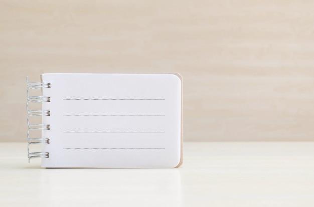 木製の机と壁に線でメモ帳のページでのクローズアップスペース