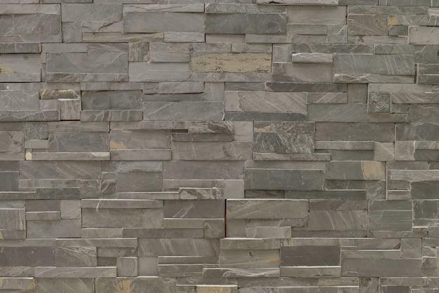 クローズアップ表面レンガ模様の古い黒い石レンガの壁のテクスチャ背景