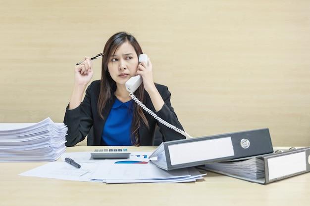 クローズアップ女性のドキュメントファイルを操作し、彼女の手でオフィスの電話を保持