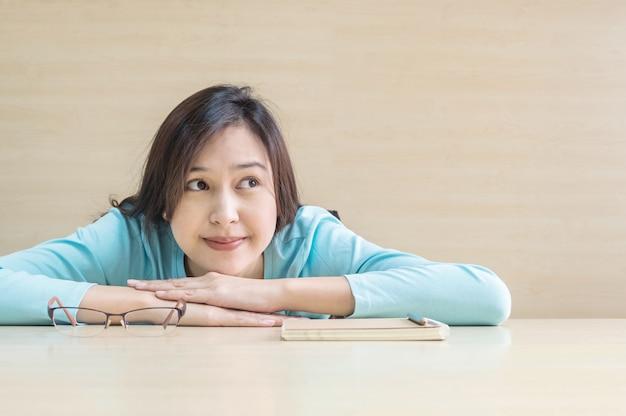 Азиатская женщина крупным планом лежала на столе с счастливым лицом во время отдыха от чтения книги