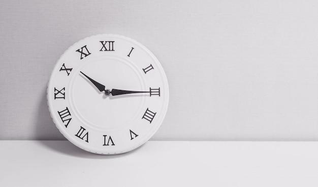 Крупным планом белые часы для украшения шоу четверть одиннадцатого