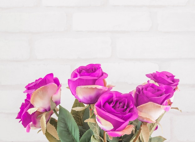 クローズアップ人工ファブリックピンクのバラの花を飾る白いレンガの壁のテクスチャ背景