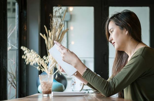Крупным планом женщина, читающая книгу в кафе с счастливым лицом