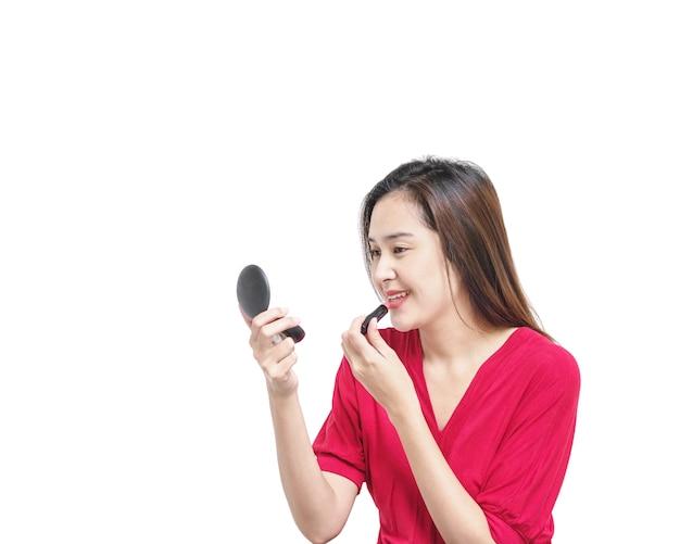 クローズアップアジアの女性は白い背景で隔離の口紅によって補っています。