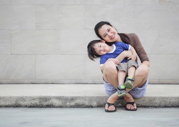 コピースペースと大理石の壁のテクスチャ背景の楽しい動きで彼女の息子を保持しているクローズアップアジアの母