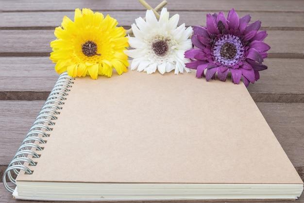 ぼやけている古い木製テーブルテクスチャ背景にカラフルな偽花と茶色のノートブック