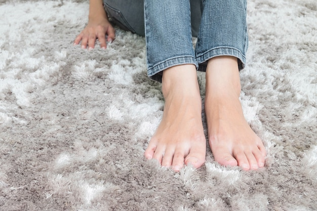 灰色のカーペットの床の家の中でテクスチャ背景の上に座ってアジアの女性の足をクローズアップ