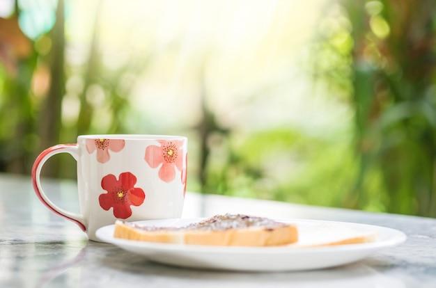 朝は大理石の机と庭の景色にクローズアップかわいいカップ