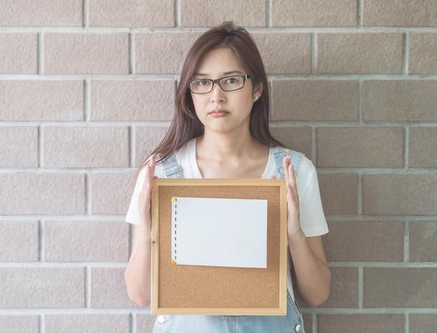 眉をひそめて顔を手にコルクボードを持つアジアの女性